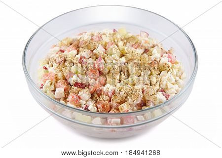Cottage cheese tomatoes cucumbers and radishes cut into cubes and mixed with spices in a glass bowl on a white background