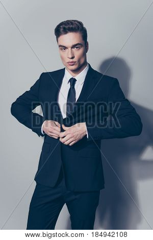 Ideal! Handsome Young Businessman With Perfec Hair Is Closing His Jacket, Standing On The Pure Light