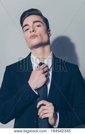 Close Up Portrait Of Attractive Businessman Fixing His Tie On The Light Background. He Looks Straigh