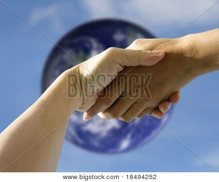 A pair of hands holding or shaking each other against a blurred earth. Concept: Agreeement reached or helping hand.