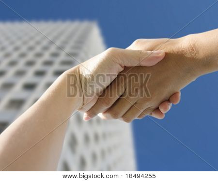 A pair of hands holding or shaking each other against a building background. Concept: Business deal done.