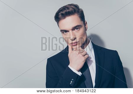 Close Up Portrait Of Young Handsome Guy Looking In The Camera, Touching His Fsce. He Is Wearing Suit
