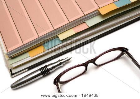 Carpeta, pluma y gafas