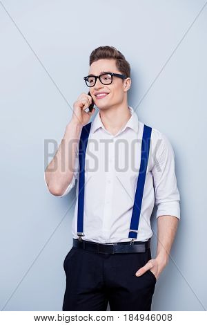 Attractive Young Man In White Shirt And Suspenders, Glasses Is Standing On The Pure Light Background
