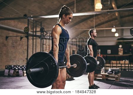 Sportive Serious People Lifting Barbells In Gym