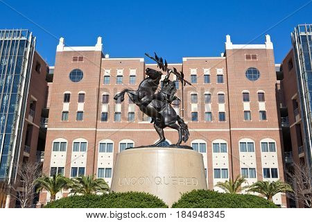 TALLAHASSEE FLORIDA - FEBRUARY 11 2017: The Unconquered statue of a Seminole Indian riding a horse is outside Doak S. Campbell Stadium on the campus of Florida State University in Tallahassee Florida on February 11 2017.