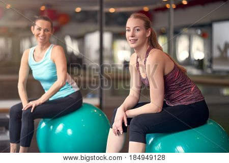 Two healthy young women with pilates or gym balls taking a break from their workout in a gym sitting smiling at the camera in an active lifestyle and fitness concept