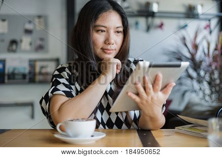 woman shopping online using laptop tablet in coffee shop happy face / woman shopping online