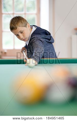 10-year-old kid learning how to play pool