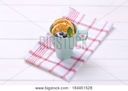 cup of american pancakes with yogurt and fresh blueberries on checkered dishtowel