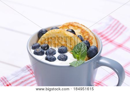 cup of american pancakes with white yogurt and fresh blueberries on checkered dishtowel - close up