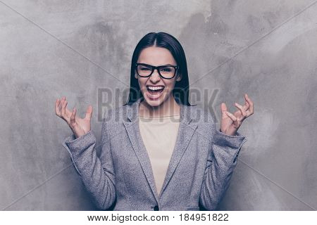 Close Up Portrait Of Shouting Mad Brunette Woman In Glasses And Jacket At Grey Background