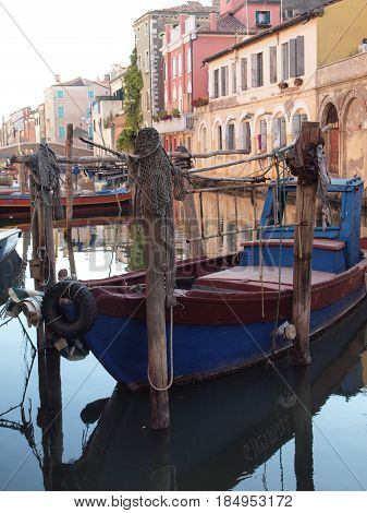Chioggia, Italy.  Palaces, canal. Boats moored with wooden poles.