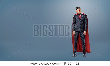 A sad businessman in a superhero red cape standing on dark blue background with his shoulders slumped. Business and risk. Failure and doubt. Unexpected trouble.