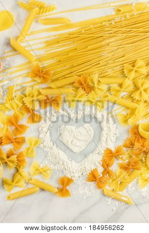 Various types of pasta on a white marble table, with a heart drawn in flour and a place for text