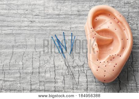 Needles for acupuncture and plastic mockup of human ear on grey background