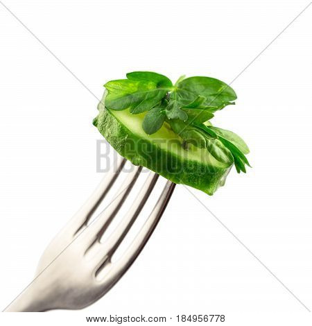 Slice cucumber and parsley impaled on fork isolated on white background close-up view.