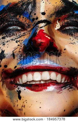 Smiling insane Clown Woman with white Eyes and Paint Stains on Face
