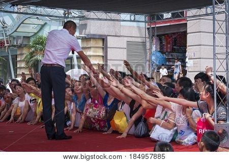 Xian China - August 6 2012: Group of people gather in front of a street shop and try to reach a seller who is selling mobile phones in Xian China