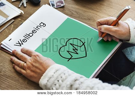Hands drawing a wellbeing heartbeat icon on a tablet