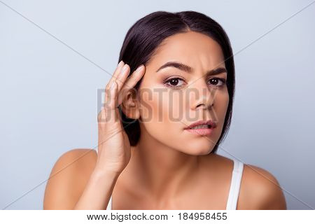 Cose Up Photo Of Pretty Young Latin American Woman Touching Her Face And Look Serious