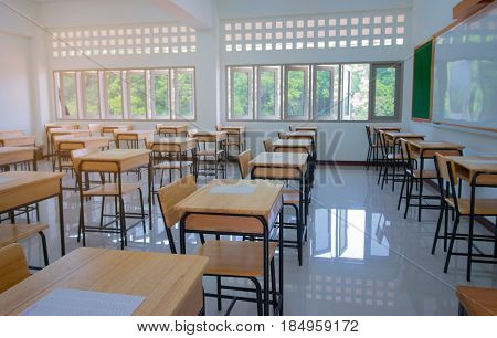 School classroom with test exam paper on desks chair wood and blackboard at high school thailand education concept