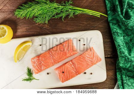 Two slices of salmon on a dark background with wedges of lemon, peppercorns, and dill sprigs, shot from above, with a place for text
