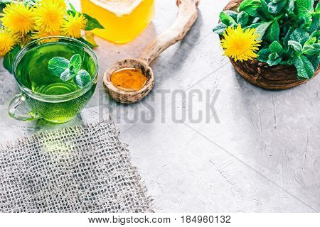 Green mint tea in translucent glass tea cup and honey in rustic spoon on concrete background with dandelions and fresh mint
