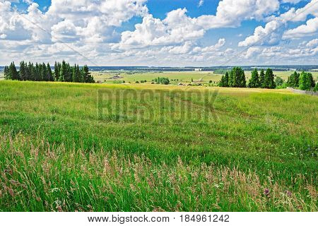 Russian village surrounded by forests and fields at summer day