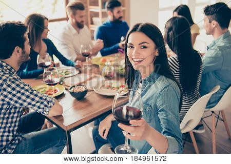 Close Up Of A Girl Looking At The Camera Holding Glass Of Red Wine And Smiling. She Is Posing To Pho