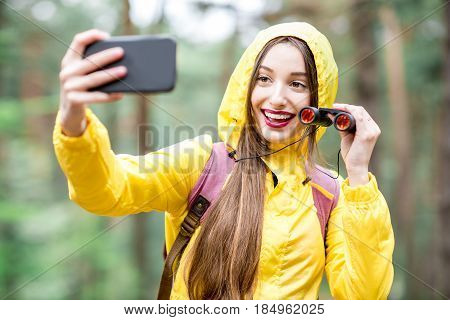 Young woman in yellow raincoat taking selfie portrait while hiking with binoculars and backpack in the green forest