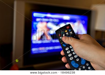 Hand pointing a tv remote control towards the television.