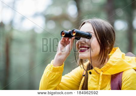 Young woman in yellow raincoat hiking with binoculars and backpack in the green pine forest