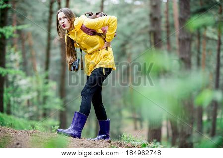 Young woman in yellow raincoat having a trouble feeling knee pain during the travel in the forest
