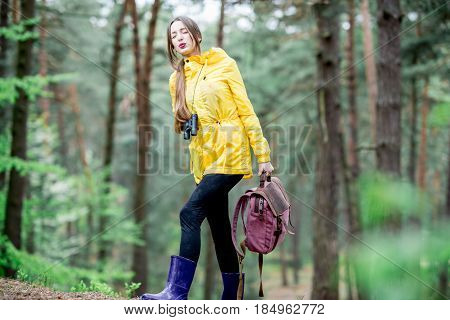 Tired woman in yellow raincoat carrying a heavy backpack while traveling in the green forest