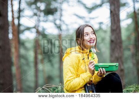 Young woman having a snack with healthy food in lunch box during the traveling in the forest
