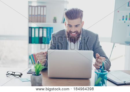 Frustrated Young Bearded Businessman Yelling At His Laptop In Office. He Is Angry Because Of Big Mis