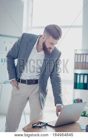 Confident Young Man Is Checking Information At His Laptop Before Going To A Meeting With Businesspar