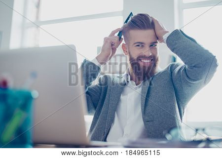Handsome Young Man Is Fixing His Hair At The Work Place. He Is Smiling, Wearing Smart Suit