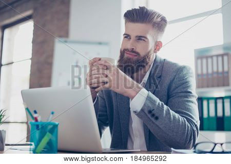 Young Dreaming Worker Is Thinking In Front Of Laptop At Work Place. He Is Happy, Smiling