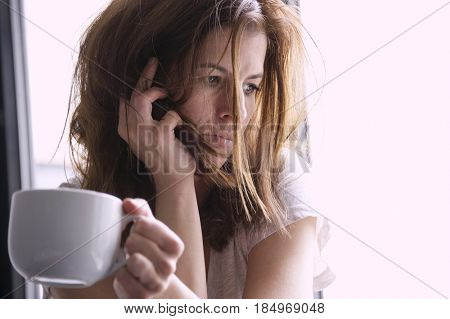 Tired and sad woman is sitting in the window seat with a cup in her hand. Depression concept.