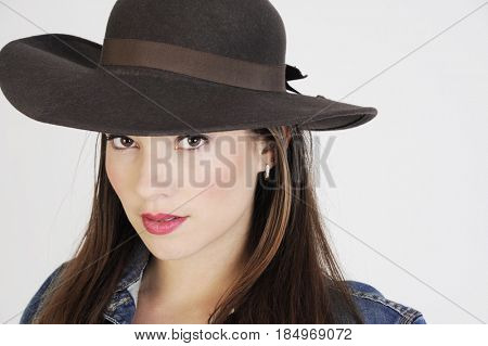 Closeup portrait of an attractive young hipster woman in a brown hat. Isolated on white.