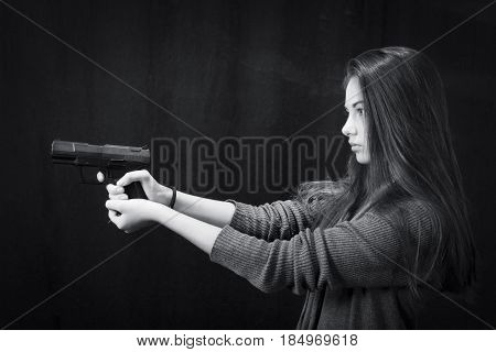 Monochrome close up emotional portrait of young beautiful girl with a gun