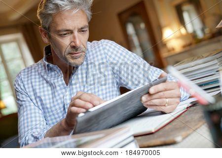 Mature man at home sitting at desk and using digital tablet