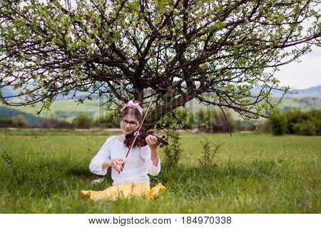 Beautiful blonde girl sitting on a beautiful green grass full of flowers and enjoy the sounds of the violin girl playing the violin in the countryside on a beautiful meadow