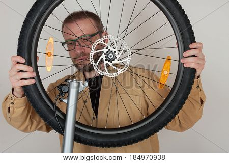 Bearded Man Puts The Front Wheel On The Bicycle.