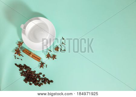 cup of coffee, Cardamom, grains of coffee and cinnamon on a turquoise background