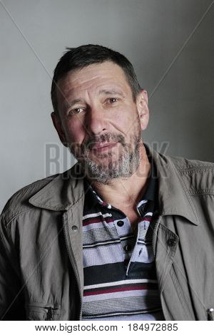 Portrait of serious man with beard tilted his head to side of the shoulder and looking straight into the lensn