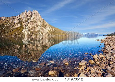Picturesque mountain in the city of San Carlos de Bariloche, Argentina. The mirror water of shallow lake reflects sharp rocks. The concept of exotic and extreme tourism