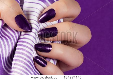 Female hand with dark purple nails is holding purple textile on purple background.